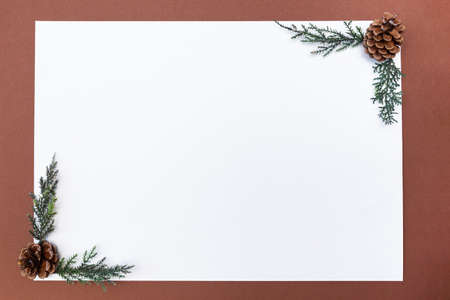 Blank sheet of paper on a brown background, composition with pine cones. Winter background with space for text, mock up.