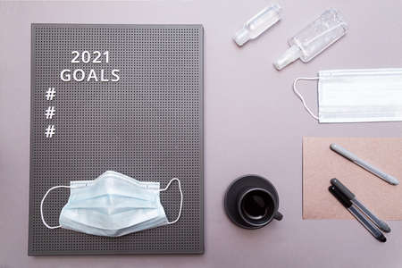 Concept of goals 2021. Face protective mask, hand sanitizer bottles, an espresso cup, and a sheet of paper with markers and white text and numbers on a gray board.