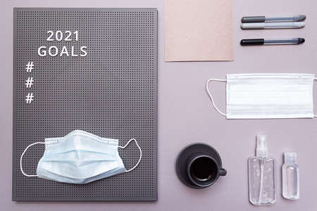 Concept of goals 2021. Face protective mask, hand sanitizer bottles, an espresso cup, and a sheet of paper with markers and white text and numbers on a gray board. Stock fotó