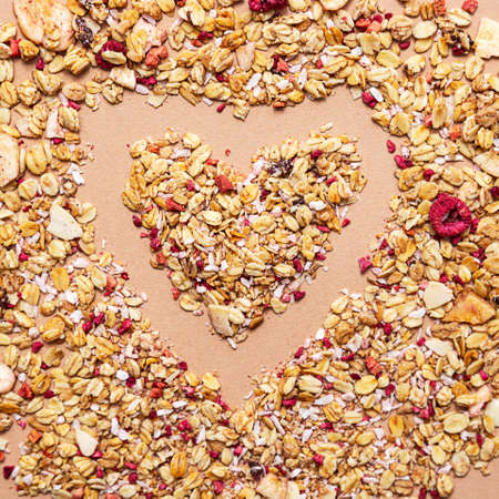 Heart shape made of granola on a beige background. Healthy food concept
