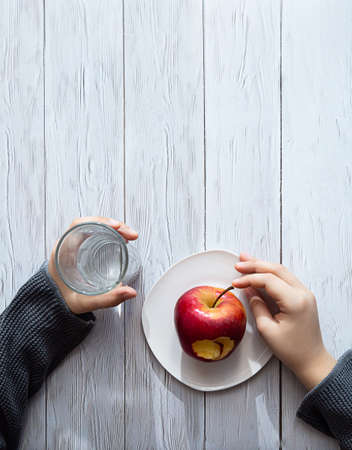 Minimal healthy snack concept. The child's hands are holding an apple and a glass of water. Still life on a light wooden table with shadows and highlights of sunlight.