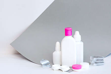 Contact lenses and accessories still life on a gray-white background. Composition with solution bottles and lens case with copy space