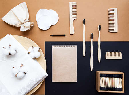 Zero waste lifestyle concept. Blank notebook, bamboo toothbrushes, hairbrushes, ear sticks, reusable cotton sponges. Flat lay on a beige background.