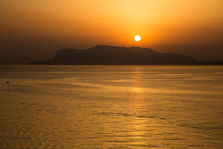 The sun has peeked over the mountains and the sea in Sicily, creating a golden orange stripe on the water Foto de archivo