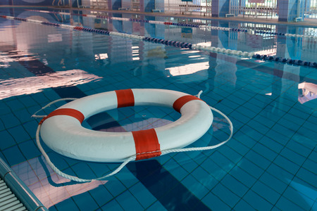 perry: A red and white lifebuoy (Kisby Ring) floating in a covered swimming pool Stock Photo