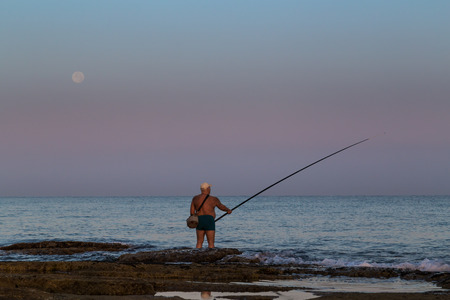 A fisherman with a fishing rod with his feet in the water with a full moon in the backgroud at dawn