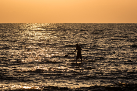 sup: Silhouette of a young man on his sup paddle board during a clear sunset