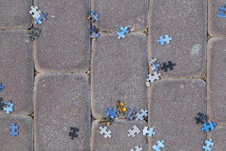 the thrown: Puzzle pieces thrown randomly on paving stones Stock Photo