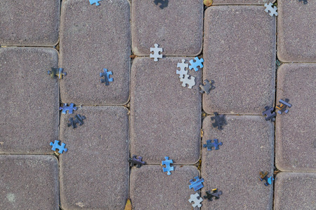 enigma: Puzzle pieces thrown randomly on paving stones Stock Photo