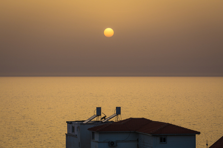 warm water: A clear sky sunset over Nahariya beach with silhouettes of 2 warm water sun collectors Stock Photo