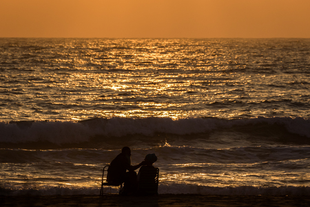caresses: Silhouette of a romantic couple by the sea during sunset, the man caresses tenderly his wife