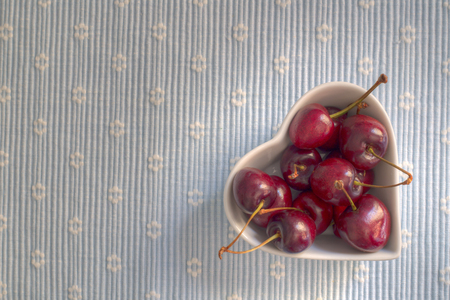 painterly: Shining dark cherries in a heart shaped bowl on a fabric background, painterly