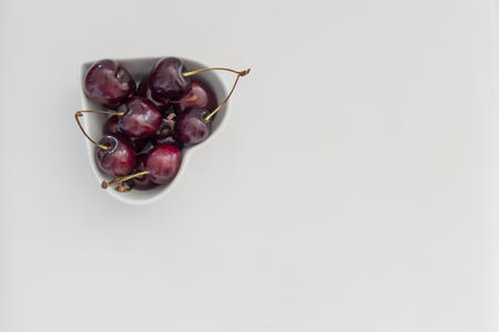 painterly: Shining dark cherries in a heart shaped bowl on a white background, painterly Stock Photo