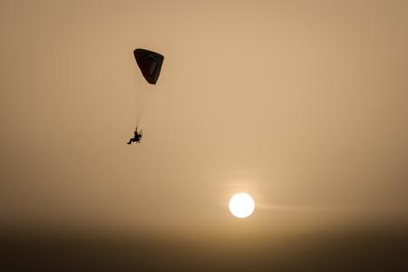 Silhouette of a Propelled Paraglider on a clear sunset sky Stock Photo