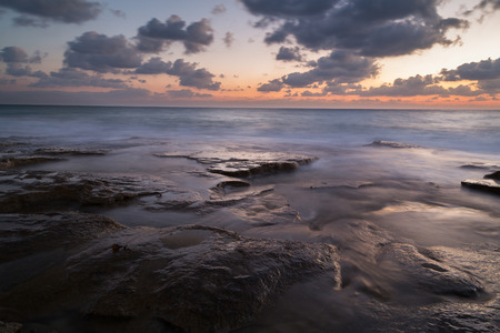 Long exposure creating dreamy silky water effect on the rocks after sunset, Nahariya Beach Stock Photo