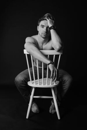 Muscular and fit young bodybuilder fitness male model posing on chair. Black and white photo. body, smile and chorism