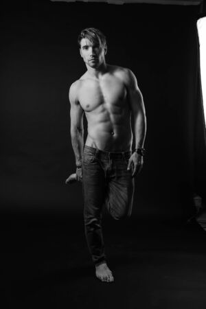 black and white studio shoot of strong athletic man on dark background. sexy body