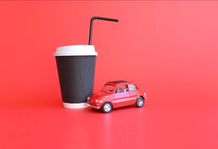Design concept of mockup coffee cup and little red toy car isolated on red background. Copy space for text and logo.