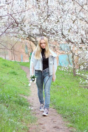 A beautiful young girl in jeans and sneakers walks along the path against the background of flowering white trees Standard-Bild