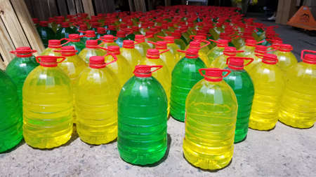 Several plastic gallons with red lid. many plastic gallons of colored liquid. wholesale gallon warehouse