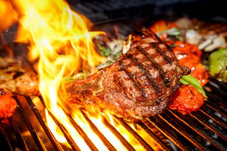 steak cooking on fire with vegetables