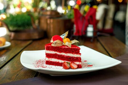 red velvet cake on a plate with strawberries on a wooden table