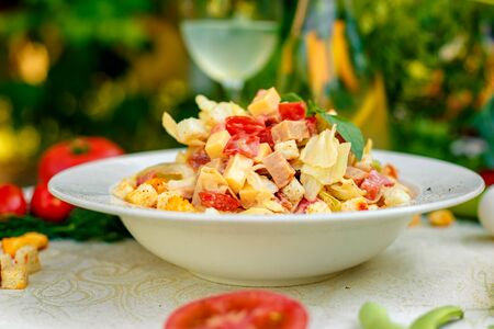 fresh salad with chicken, cheese, rusks, lettuce and tomatoes