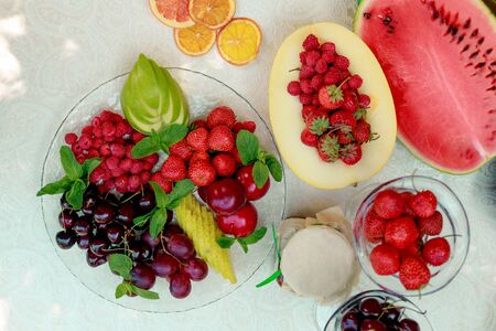 berries and fruit in a transparent plate. Apples, pears, cherries, raspberries, plums, grapes.