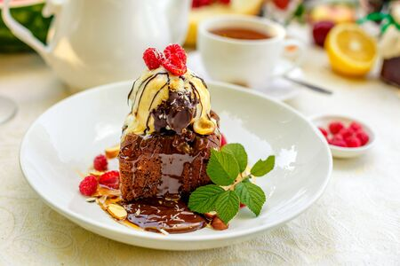 chocolate sponge cake with ice cream and fruit on a served table