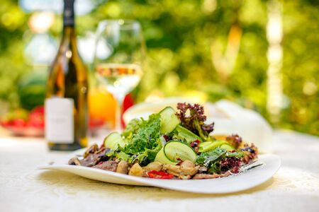 warm salad with meat, cucumber and vegetables on a white plate on the table