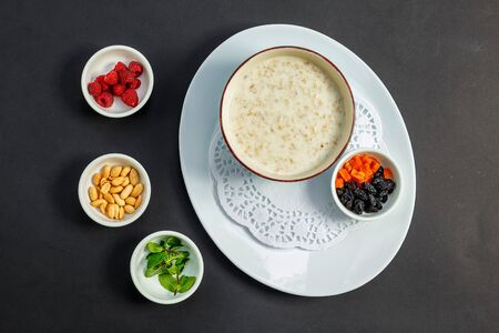 rice porridge with milk, healthy breakfast with raisins, nuts, mint on a white plate
