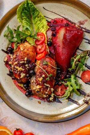 chicken thighs with rucola, nuts and vegetables on a decorated table Imagens