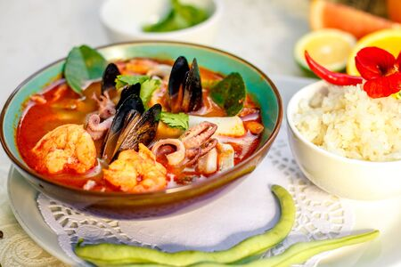 Thai soup tom yam with seafood (octopus, shrimps), herbs and vegetables served on the table with ingredients, healthy food