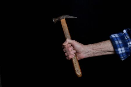closeup of a hand of an old man holding vintage rusty shoe hammer with wooden handle isolated on black background Stock Photo