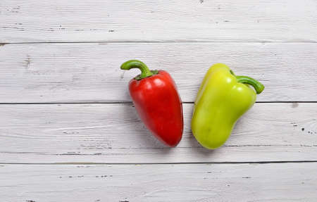 top view of red and yellow peppers on old rustic white wooden table, copy space