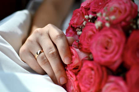 Hand of bride holding a beautiful colorful blooming bouquet of roses, lie on the white bed