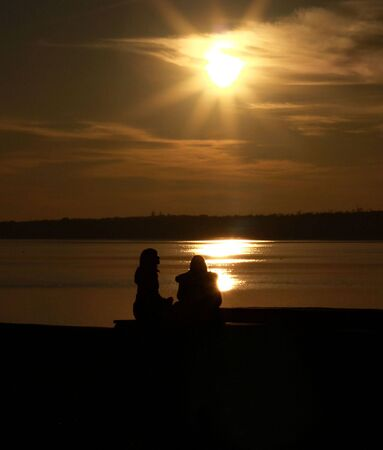 Two girls in the sunset near the river Banco de Imagens