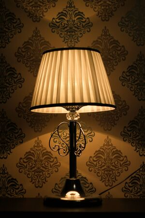 Picture of a bedside silver lamp, which is standing on a bedside table with a white lampshade at night. It creates a romantic and calm atmosphere. Shades are on the walls with a silver wallpaper