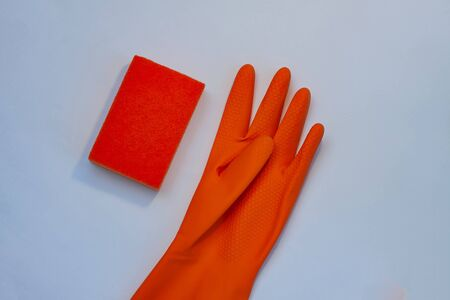 One orange glove for cleaning with an orange wisp on a grey background