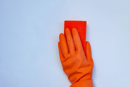 One orange glove for cleaning with an orange wisp on a grey background with a copy space