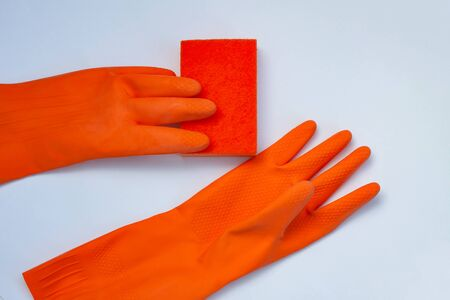 2 orange gloves for cleaning with an orange wisp on a grey background