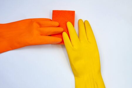 orange and yellow gloves for cleaning with an orange wisp on a grey background
