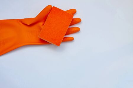 orange glove for cleaning with an orange wisp on a light background with a copy space