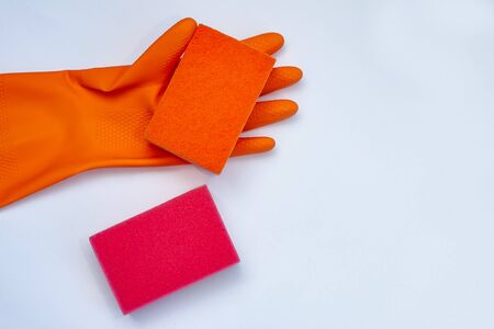orange glove for cleaning with  orange and red  wisps on a grey background with a copy space Zdjęcie Seryjne