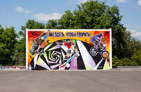 """Graffiti painted wall with a text translation:""""We are here to create"""". This wall is in the skateboarders place in the city Nikolaev"""