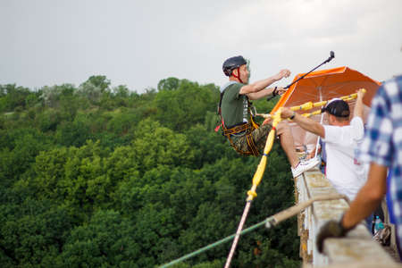 Concept of Extreme Sports and Fun. A man is a thrill-seeker and a rope jumper from the bridge. He is very happy to make a dream come true. He is holding an action camera and insanely happy