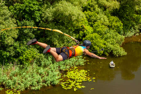 Ivanovsky Bridge, Ukraine - June 21, 2020: Concept of Extreme Sports and Fun. A man is doing rope jumping from the bridge. He is very happy to make a dream come true. He is sporty and in a good form Éditoriale