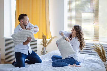 A beautiful curly pregnant girl plays with her husband on a bed in the morning. They are holding pillows and pay games. They have a family look: white shirts and jeans. Family and Happiness Concept