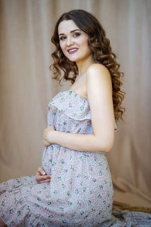 A beautiful young curly pregnant girl in a light dress sits on the floor near curtain. She is embracing her belly with both hands and looks into the camera. Concept of pregnancy and motherhood