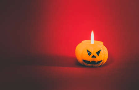 One scary orange pumpkin shaped candle with a fire, isolated on red background, space for text. Tradition Happy Halloween concept. Dark tones picture